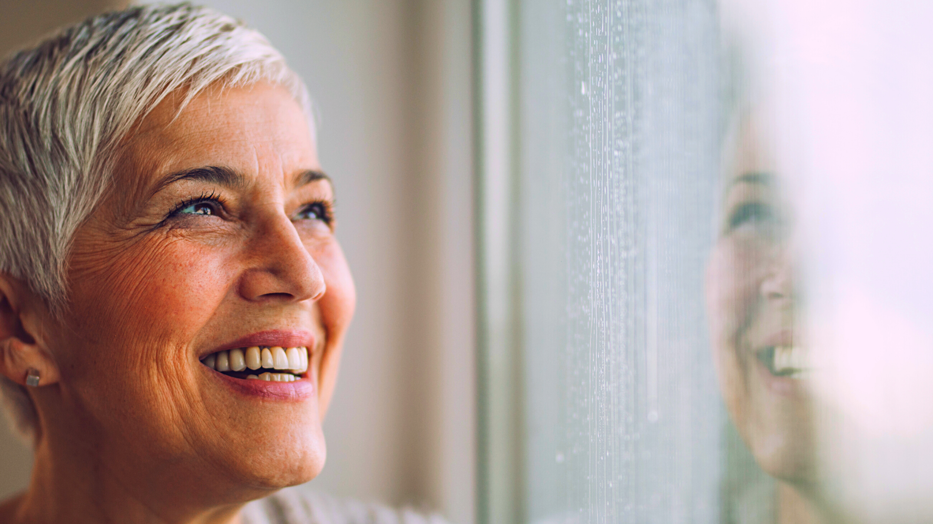 Older woman looking out window smiling and hopeful