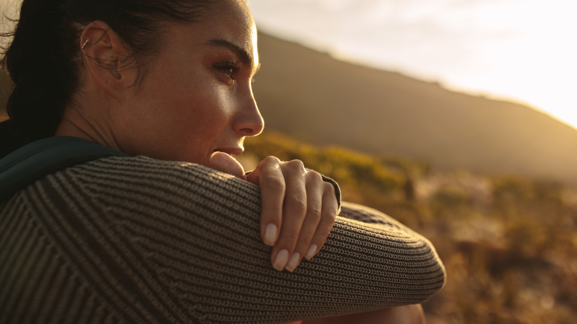 woman gazing toward a setting or rising sun with hills or mountains in the background